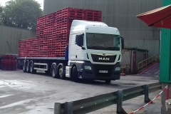 MAN tractor unit with flatbed trailer loaded with pallets