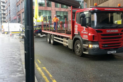Scania Rigid truck flatbed with steel being unloaded with a crane